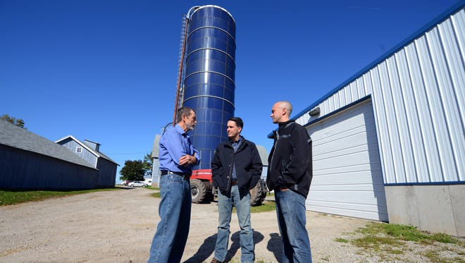 Wisconsin Gov. Scott Walker, center, talks with farm owners Raymond Diederich, left, and his son Daniel on their De Pere dairy farm Thursday, October 9, 2014.
