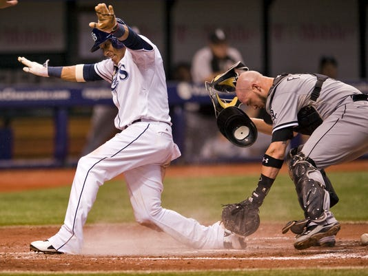 Chicago White Sox catcher Tyler Flowers, right, looks for the ball as Tampa Bay Rays' Yunel Escobar scores on Ben Zobrist's RBI-single during the inning of a baseball game Saturday, Sept. 20, 2014 in St. Petersburg, Fla. (AP Photo/Steve Nesius)