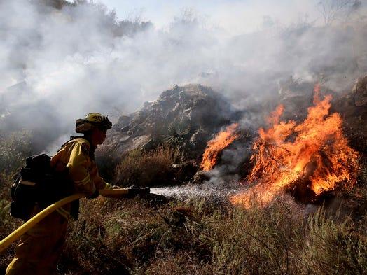 Firefighter Jeff Newby battles the Colby Fire on Jan. 17 near Azusa, Calif.
