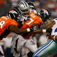 ARLINGTON, TX - AUGUST 28:  Phillip Tanner #28 of the Dallas Cowboys is tackled by Corey Nelson #47 of the Denver Broncos and Kevin Vickerson #99 of the Denver Broncos in the first half of their preseason game at AT&T Stadium on August 28, 2014 in Arlington, Texas.  (Photo by Tom Pennington/Getty Images)