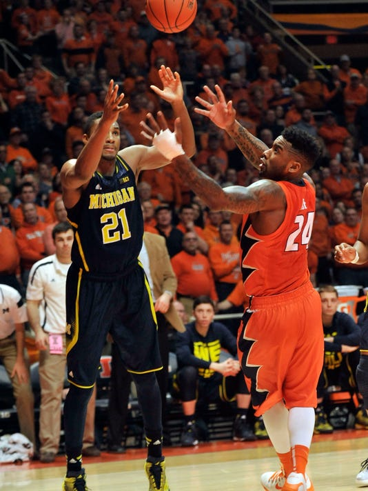 Illinois' Rayvonte Rice (24) grabs a loose ball away from Michigan's Zak Irvin (21) in overtime of an NCAA college basketball game in Champaign, Ill., on Thursday, Feb. 12, 2015. Illinois won 64-52. (AP Photo/Rick Danzl)