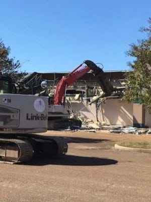 Heavy equipment begins tearing off the facade of the annex east of Lakeland Factory Outlet Mall. The demolition of the building is the start of clearing the property for the Lake District development at Interstate 40 and Canada Road in Lakeland