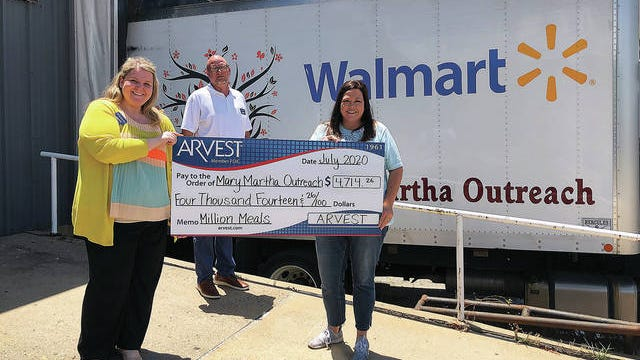 Arvest sales manager Whitney Watson and Arvest loan manager David Nickel recently presented a donation of $4,714.26 to Misty Wishall, executive director of Mary Martha Outreach, to help fight hunger in Bartlesville and surrounding communities. Courtesy