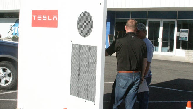 Kevin Kassekert, in the blue shirt, a director of infrastructure development for Tesla in Sparks, shows a commercial storage battery to Smith Valley resident John Abrott on April 29.