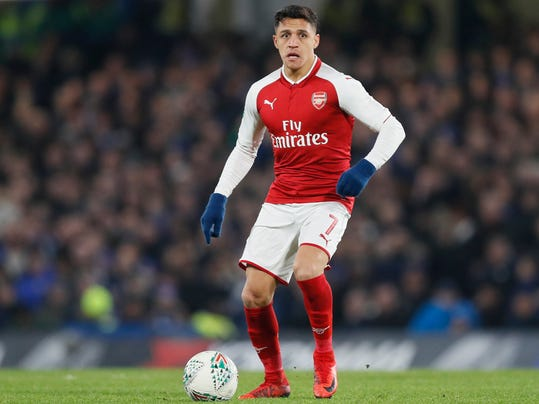 FILE - In this file photo dated Wednesday, Jan. 10, 2018, Arsenal's Alexis Sanchez during the English League Cup semifinal first leg soccer match between Chelsea and Arsenal at Stamford Bridge stadium in London.  Chilean player Sanchez has been left out of Arsenal's squad for the Premier League match against Bournemouth on Sunday Jan. 14, 2018, amid interest in the forward from Manchester City and Manchester United. (AP Photo/Kirsty Wigglesworth, FILE)