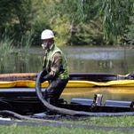 Workers from Enbridge skim oil off the surface of the Kalamazoo River on July 27, 2010, after a pipeline ruptured in Marshall, Mich. On Wednesday, July 20, 2016, Enbridge reached a $177 million settlement with the U.S. Department of Justice and the Environmental Protection Agency over oil spills.