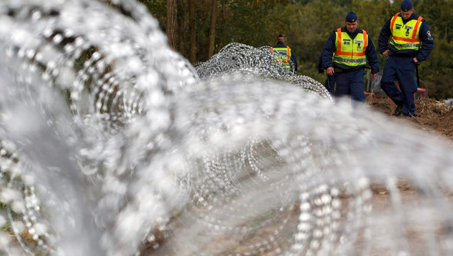 Hungarian police officers patrol the temporary fence installed at the border between Hungary and Croatia near Zakany, Hungary, Sept. 30, 2015.