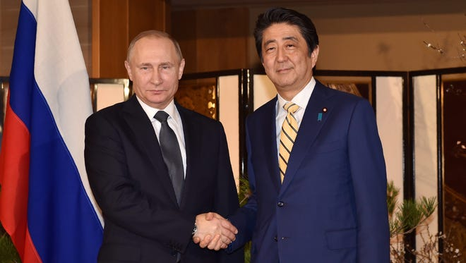 Russian President Vladimir Putin (left) shakes hands with Japanese Prime Minister Shinzo Abe prior to their talks in Nagato, Yamaguchi prefecture, Japan, Dec. 15, 2016.