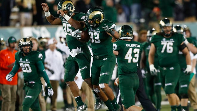 Running back Izzy Mathews (35) celebrates with linebacker Kevin Davis (33) following an interception by Davis late in the game to seal CSU's win over Utah State on Oct. 8 at Hughes Stadium. The Rams host Fresno State on Saturday.