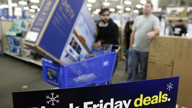 In this Nov. 22, 2018, file photo people wait in line to buy televisions as they shop during an early Black Friday sale at a Best Buy store on Thanksgiving Day in Overland Park, Kan. The holiday season was a brutal one for U.S. retailers, especially department stores and companies that sell luxury products.