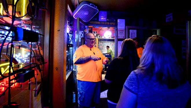 Bar manager Scott Carroll greets customers and check IDs at Stir-Ups, 123 S. Washington Street, on Friday night.