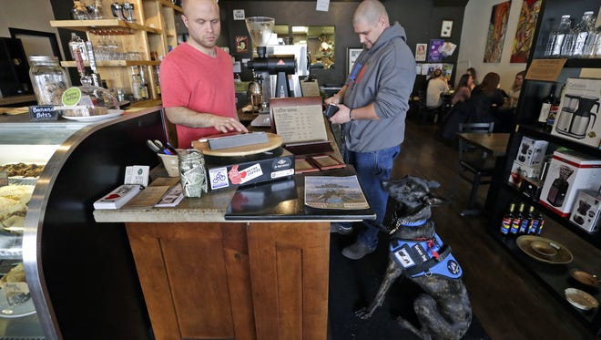 With his service dog Sig at his side, Shaun Kettner, a veteran with PTSD, orders a cup of coffee from Chase Gerow on at Seth's Coffee in downtown Little Chute, Wisconsin.