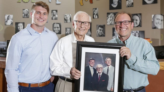 Ethan Just, left, poses for a photograph with his grandfather Dr. Harold Just and father Dr. Jeffrey Just who are holding a portrait of themselves with Dr. William W. Just in the lobby of Just Orthodontics on Reed Avenue July 19 in Manitowoc. Dr. William Just first began his dentistry practice in Manitowoc County in 1919. Ethan will be the fourth-generation Just to pursue dentistry.