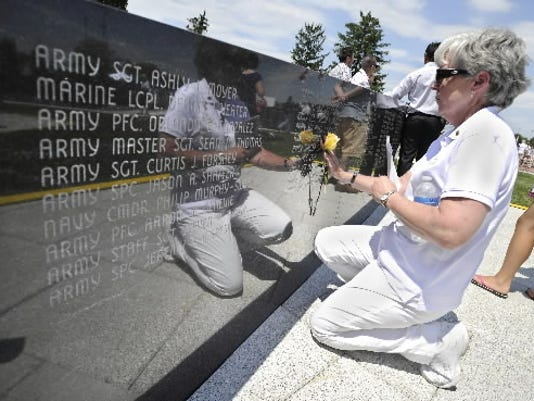 This June 2012 file photo shows Gold Star mother Fran Dembowski, of Richboro, Pa., placing a rose at the name of her son Robert, who died in Iraq, at the Veterans Memorial Gold Star Healing and Peace Garden in York.
