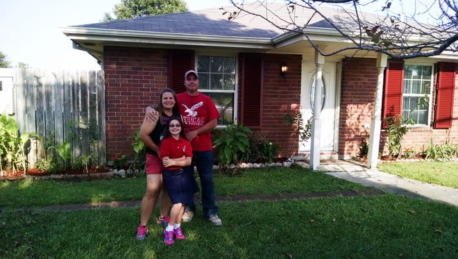Brandi Lopez, back left, stands with her husband Scott Lopez and her daughter Leanne in front of their home in Violet, Louisiana, in St. Bernard Parish on Aug. 25, 2015. The home was flooded by Hurricane Katrina 10 years ago, forcing Brandi and Scott to move to Poughkeepsie, where Leanne was born.
