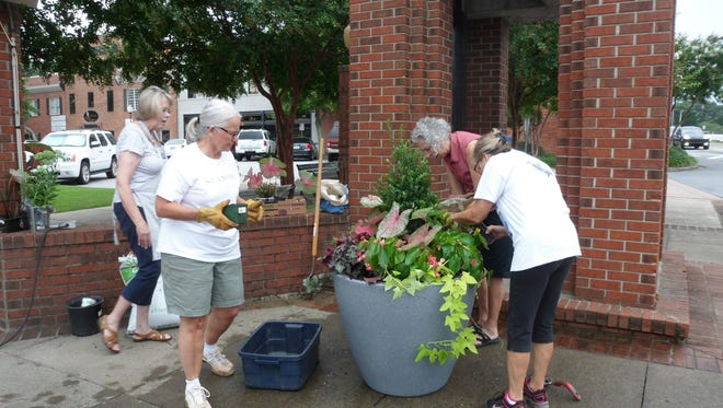 Simpsonville Garden Club members work to install a planter next to the historic clock tower in downtown Simpsonville.