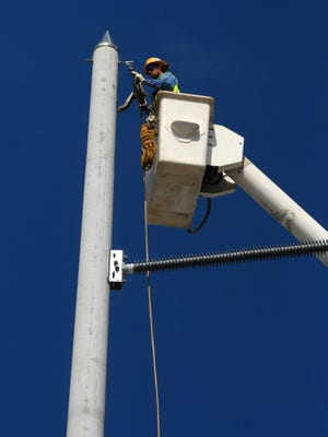 LCEC MAE YOUSIF-BASHI/The News-Press... A lineman with Pike Electric feeds rope for new Lee County Electric Cooperative transmission system on Friday along Del Prado Boulevard in Cape Coral.