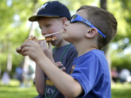 Dane Krutz, 5, and his brother Jameson Thompson, 9, dig into some pizza during a food truck rally in Pierce Park May 26 in Appleton.