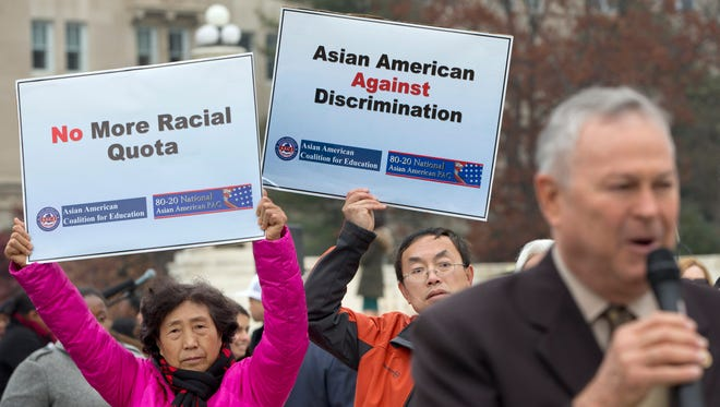 Guixue Zhou of North Potomac, Md., left, and Samuel Yan, of Loudoun County, Va., protest against racial quotas during a rally outside the Supreme Court in Washington, Wednesday, Dec. 9, 2015, as the court hears oral arguments in the Fisher v. University of Texas at Austin affirmative action case. At right is Rep. Dana Rohrabacher, R-Calif., speaking in solidarity with the Asian American Coalition for Education protest. (AP Photo/Jacquelyn Martin)