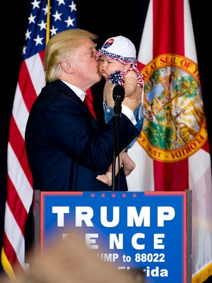 Republican presidential nominee Donald Trump kisses a baby he brought onstage Nov. 5, 2016, while speaking to a crowd of several thousand supporters in Tampa days before the end of the 2016 presidential election.
