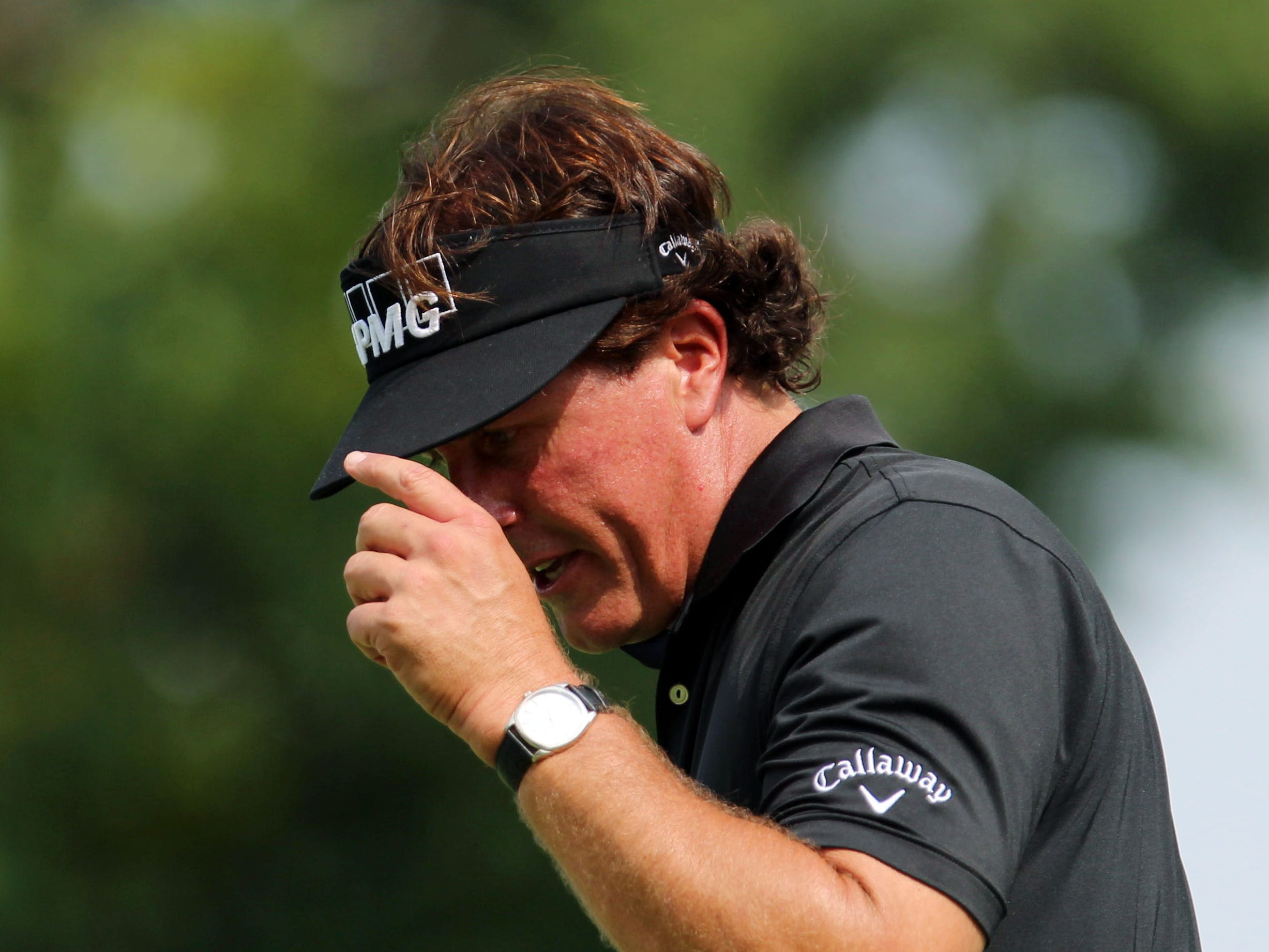 Phil Mickelson tips his hat to the gallery on the 8th green during the first round of the 95th PGA Championship at Oak Hill Country Club.