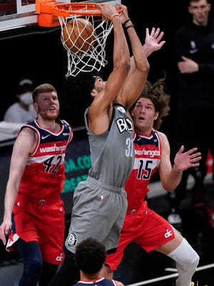 Center Jarrett Allen, shown dunking, is the key player the Cavs acquired in a four-team trade which was finalized Thursday. [Kathy Willens/Associated Press]