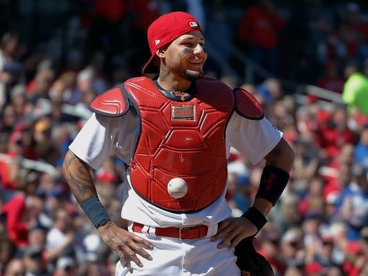 FILE - In this Thursday, April 6, 2017, file photo, St. Louis Cardinals catcher Yadier Molina stands with his hands on his hips as a ball is somehow stuck to his chest protector during the seventh inning of a baseball game against the Chicago Cubs in St. Louis. The ball was stuck to Molina's chest protector on a dropped third strike allowing the Cubs' Matt Szczur to reach first base when Molina couldn't find the ball. The baseball that curiously stuck to Molina's chest protector during the game was sold for $2,015 in a St. Louis Cardinals online auction. There were 58 bids for the ball, and the winner was declared when the auction closed Sunday night, April 17. (AP Photo/Jeff Roberson, File)
