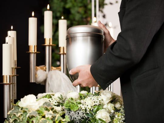 An urn being held.