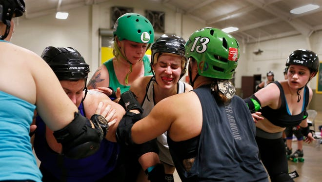 Capital City Roller Girls' Ashley Bleicher, aka Track Queen, center, attempts to break through the group during practice at the Brandon Armory on May 11.