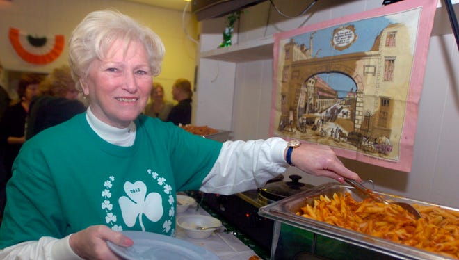 Carol Hennessey, organizer of the St. Patrick's Day Parade in Royal Oak, scoops up some all you can eat mostaccioli at the fundraiser for the parade.