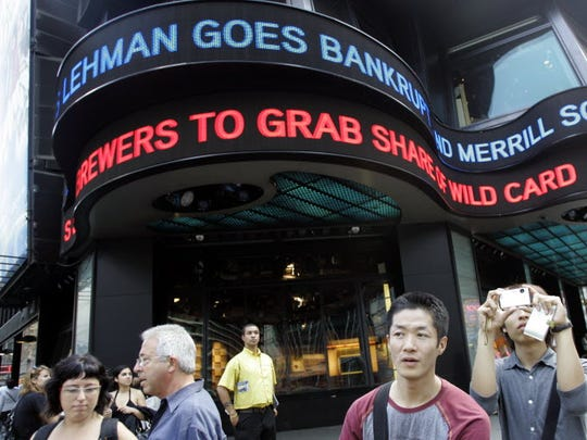 In this Sept. 15, 2008, tourists take pictures in New York's Times Square as the days financial news about the bankruptcy of Lehman Brothers is displayed on the ABC news ticker.