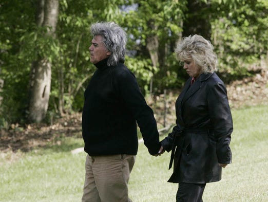 Country music singer Marty Stewart and his wife Connie Smith walk on their property to see  Johnny Cash's former home and Barry Gibb's current home burn during a fire in Hendersonville on Tuesday, April 10, 2007.