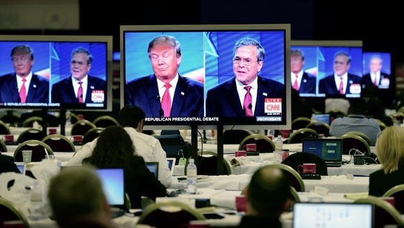 Members of the media watch Donald Trump and Bush during