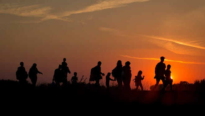 Refugees from the Middle East are silhouetted against the setting sun as they walk on railway tracks from Serbia, in Roszke, Hungary, Sunday, Aug. 30, 2015.