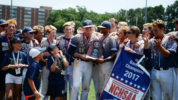 Garrett Blaylock, left, and Collin Watt share the NCHSAA 4-A championship trophy after Roberson's win on June 3 at N.C. State.