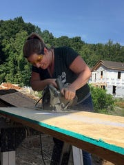 Reporter Beth Walton cuts a piece of plywood while volunteering for nonprofit affordable housing provider Mountain Housing Opportunities. The agency's Self--Help Homeownership Program allows low-income families to build their own neighborhoods in exchange for competitive mortgages and low-interest rates.