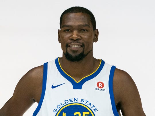 Kevin Durant poses in his Warriors jersey, which features
