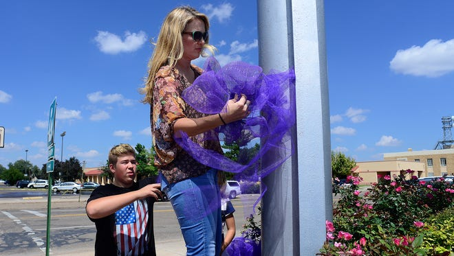 Fifteen-year-old Dillan Spear, left, helps his mom Lisa Pellegrino-Spear put a purple ribbon on a light pole across the street from the Clovis-Carver Public Library in Clovis, N.M., Tuesday, Aug. 29, 2017, a day after a deadly shooting in the library that killed two and wounded four.