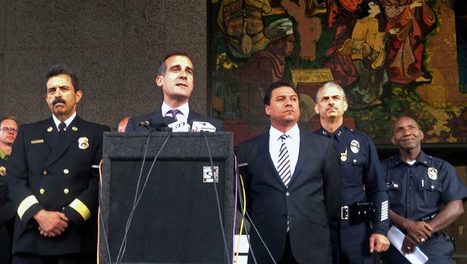 Los Angeles Mayor Eric Garcetti, second from left, surrounded by city authorities, comments on the arrest by the Los Angeles Police Department's anti-terrorism division of a suspect on suspicion of arson, during a news conference in downtown Los Angeles on Wednesday, May 27, 2015.