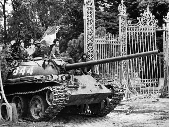 A North Vietnamese tank rolls through the gates of