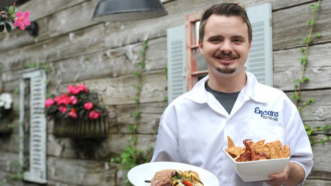 Encore Bistro & Bar co-owner and chef Tyler LaChance holds the duck breast entree, left, and corn and bacon guacamole, one of the dishes he says is especially good for takeout. Freshly made guacamole comes with house-fried tortilla chips..