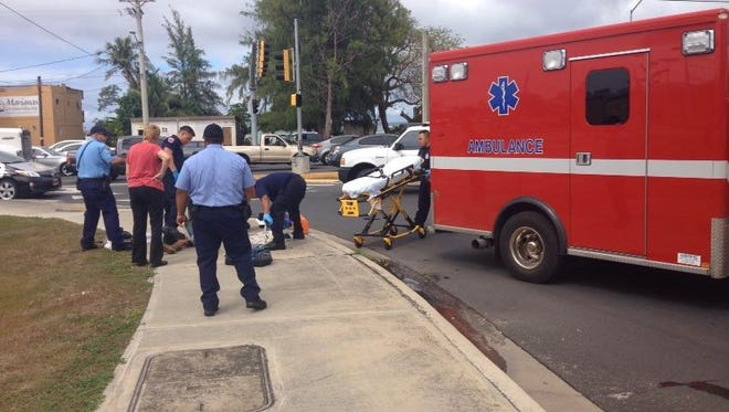 Medics tend to a 52-year-old man lying on a sidewalk near the  Route 1 and Route 8 intersection in Hagåtña on Wednesday, Feb. 3. The man was later taken to Guam Memorial Hospital where he was reported as responsive.