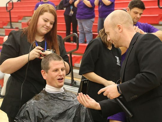 Harding High School assistant principal Todd Schneider shows guidance counselor Mike Vyrostek a picture during a pep rally on Nov. 17 where 16 faculty members got their heads shaved.