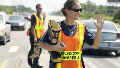 """Helping """"Jerry's Kids"""". Christina Romano ,and Laddie Rutkowski, both Firefighter/ Paramedics with BCFR station #80, in Suntree area, fill the boot at intersection of Wickham Road and Pineda Causeway. BCFR Firefighters helping out the MDA (Muscular Dystrophy Association. ) Sunday was the final day for """"Fill the Boot"""" for Jerry's Kids, They had been out Friday and Saturday, as each shift with BCFR took turns at popular intersections, retail stores, etc. To give to MDA, their web site is www.mdausa.org."""