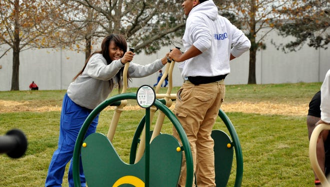Anainis Ellis and Ricardo Black from Woodward Career Technical High School take a turn on the new exercise equipment at Roselawn Park during the Nov. 18 ribbon cutting of the outdoor gym and fitness track at Roselawn Park.