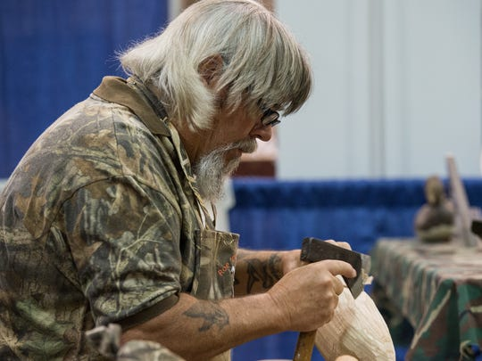 "Roe ""Duc Man"" Terry carves a decoy with a hatchet during"