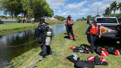 Fire Rescue personnel work at the edge of a canal near Military Trail and Camino Real in suburban Boca Raton on Sunday, Feb. 23, 2020, after a vehicle went into the water.