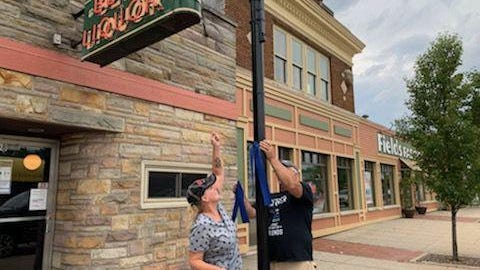 Spring Lake Township residents Lee and Jim Patterson hang blue ribbons on village lamp posts earlier this week as a tribute to police officers. The village manager says such actions are not allowed and had the ribbons removed the next day.