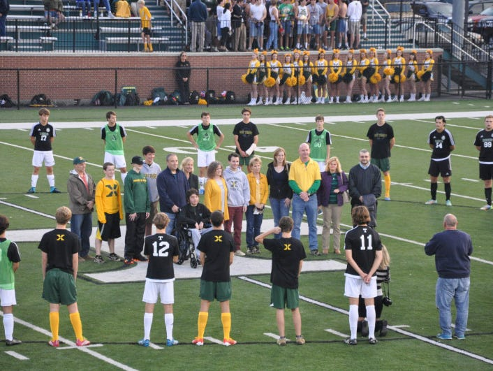 Students and parents gather for a recognition of Childhood Cancer Awareness Month during the St. X/Trinity varsity soccer match on Sept. 30.