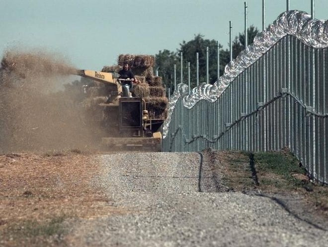 Construction crews put up fencing around the 120 acres of School at Industry land in 1998 in Rush. Youths who had been held at the county's Children's Detention Center will now be held in a new facility at Industry.